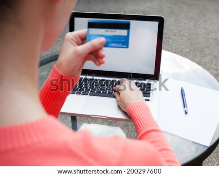 Online shopping. Woman holding credit card and using laptop computer. - stock photo