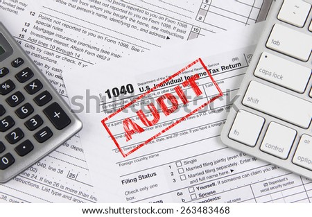 Online tax filing - federal 1040 form with computer keyboard and calculator - stock photo