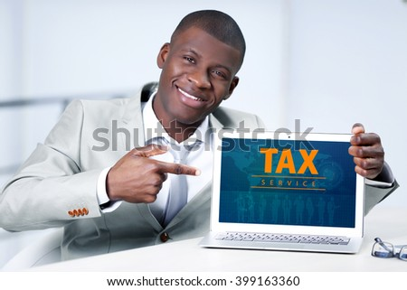 Online Tax payment concept. Handsome businessman with laptop, close up - stock photo