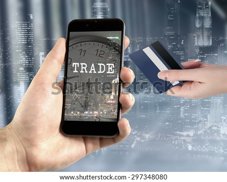 Online trading concept. Hands holding mobile phone with trade text with night view of the business city center. - stock photo