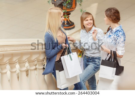 Only nice emotions from shopping. Three attractive shopping women in casual clothes holding shopping bags and talking at the stairs of the store - stock photo