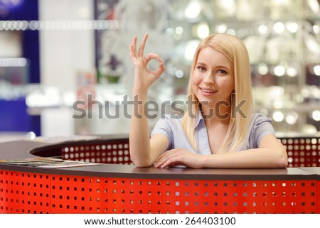 Only successful shopping.  Pretty blond receptionist on the information desk in shopping mall shows sign OK and smiles - stock photo
