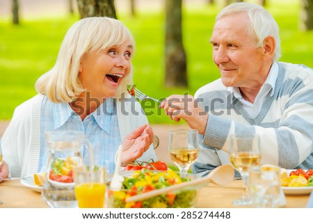 Only the best for our nearest. Senior man feeding his cheerful wife with fresh salad while both sitting at the dining table outdoors  - stock photo