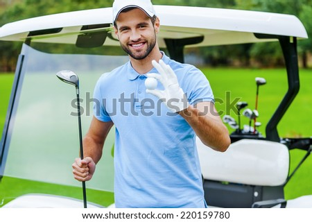 Only the best golf equipment! Handsome young smiling man holding golf ball and driver while standing near the golf cart and on golf course - stock photo