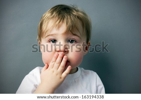 oops! cute and funny  little blond boy or toddler with hand in front of mouth - stock photo