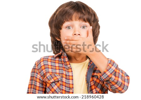 Oops! Frustrated little boy covering mouth with hand and looking at camera while standing isolated on white - stock photo