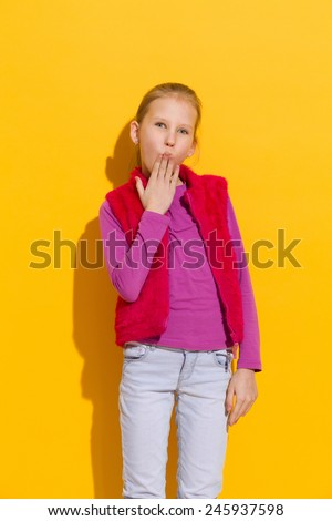 Oops! Young blond girl holding hand on her mouth. Three quarter length studio shot on yellow background. - stock photo