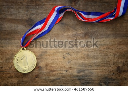 op view image of medal gold over wooden textured table