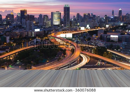 Opeing wooden floor, Aerial view city road interchanged with city background skyline night view - stock photo