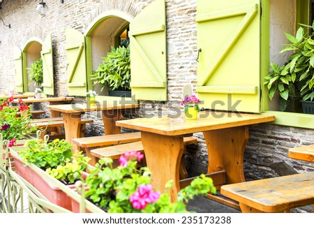 Open a beautiful terrace cafe, tables, flowers and greenery. - stock photo