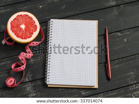 Open a blank Notepad, grapefruit, and measuring tape on a dark wooden table. The concept of a healthy lifestyle, healthy food, diet - stock photo