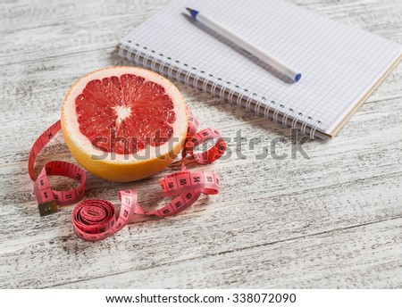 Open a blank Notepad, grapefruit and measuring tape on a light wooden table. The concept of healthy nutrition, diets - stock photo