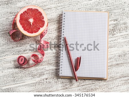 Open a blank Notepad, grapefruit and measuring tape on a light wooden table. The concept of healthy nutrition, diets, healthy lifestyle. Free space for text - stock photo