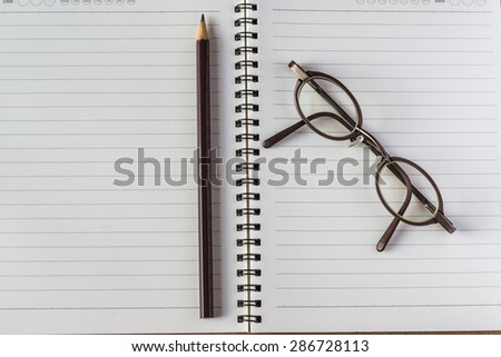 Open a blank white notebook, eyeglasses  and pencil