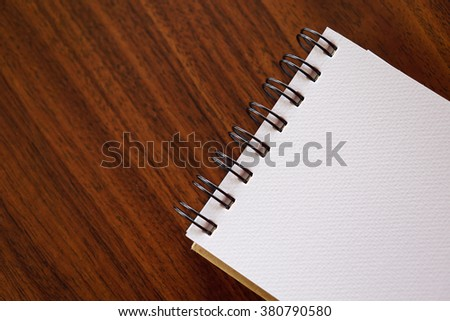 Open a blank white notebook on wooden table - stock photo