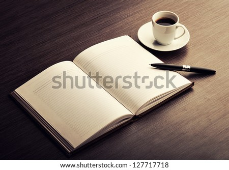 Open a blank white notebook, pen and cup of coffee on the desk - stock photo