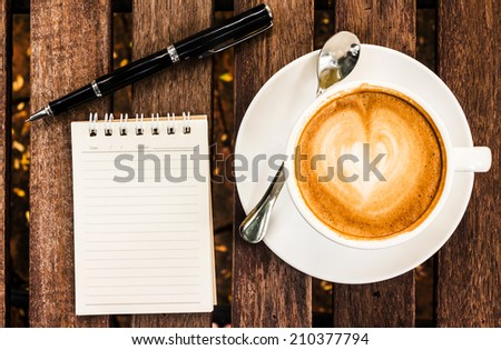 Open a blank white notebook, pen and cup of coffee on wood desk  - stock photo