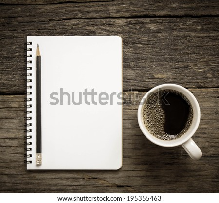 Open a blank white notebook, pencil and cup of coffee on the table