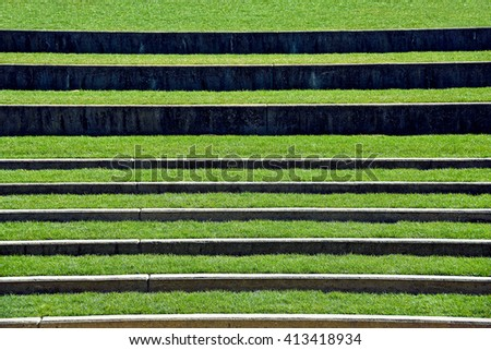 open air seating in outdoor amphitheater with grass - stock photo