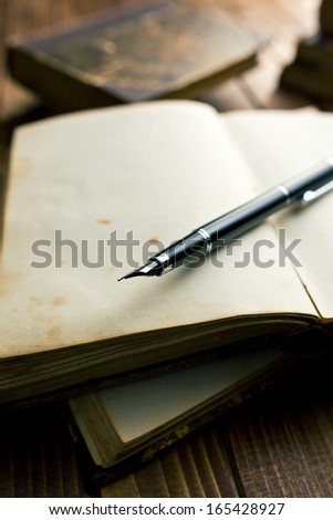 open ancient book with fountain pen on wooden table