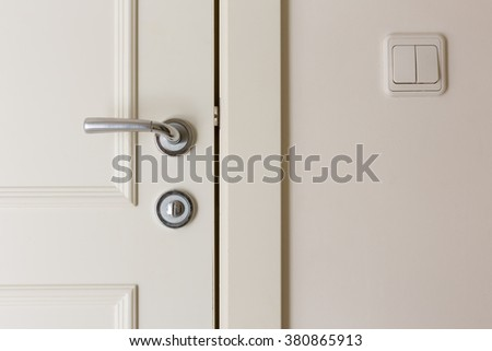 open and closed white doors close up of  handle and keyhole