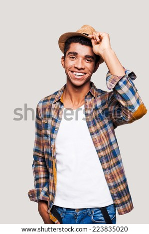 Open and sociable.  Handsome young Afro-American hipster holding hand on his hat while standing against grey background - stock photo