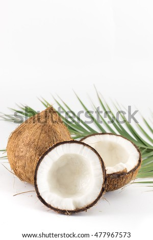 Open and whole coconuts and palm leaves on white