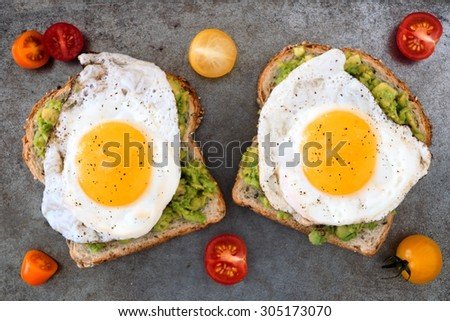 Open avocado, egg sandwiches on whole grain bread with tri-colored tomatoes on rustic baking tray - stock photo