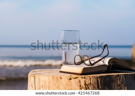 Open Bible and a glass of water on the coast - stock photo