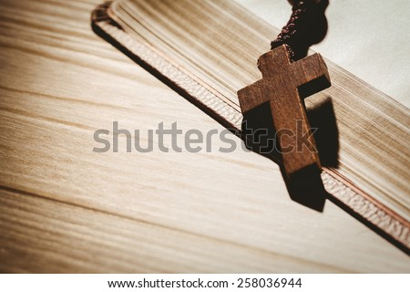 Open bible and wooden rosary beads on wooden table - stock photo