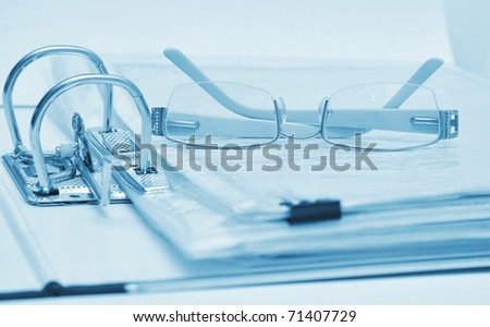 open binder and glasses over document toned blue - stock photo