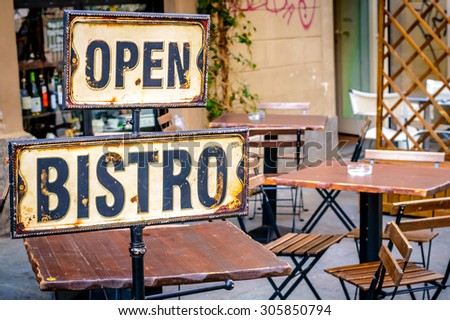 Open bistro sign at the empty cafe terrace, with empty wooden chairs and tables at the outdoor open terrace outside a restaurant or a bar, with some liquor bottles in the window out of the focus - stock photo