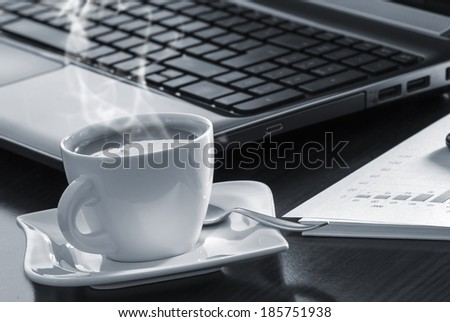 Open black laptop and hot cup of coffee on wood table