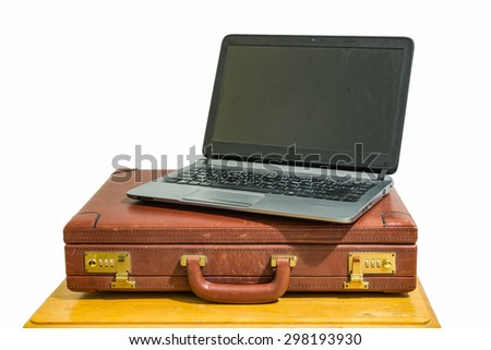 open black laptop and old vintage brown briefcase on wood table isolated - stock photo