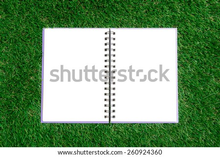 Open blank book on green grass - stock photo