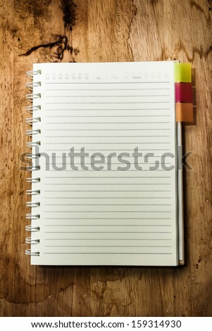Open blank book on wooden table, blank pages with line for text.