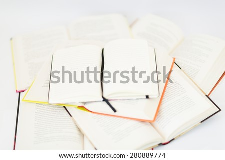 Open blank diary (notebook) on the top of different colorful books - stock photo