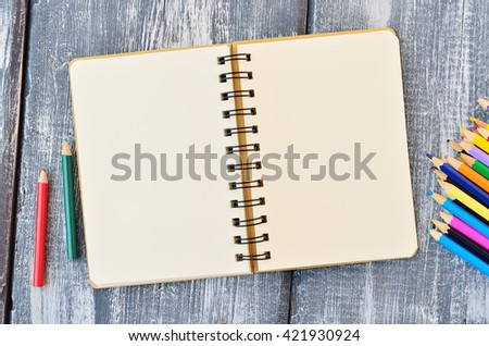 Open blank note pad and colored pencils on a wooden background