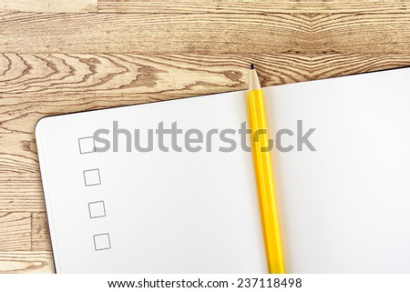 Open blank notebook with check box and yellow pencil on detail wooden table,Template mock up for adding your content - stock photo