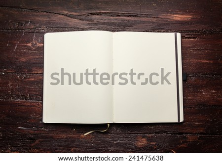 Open blank notepad with empty white pages  laying on a old dark wooden table - stock photo