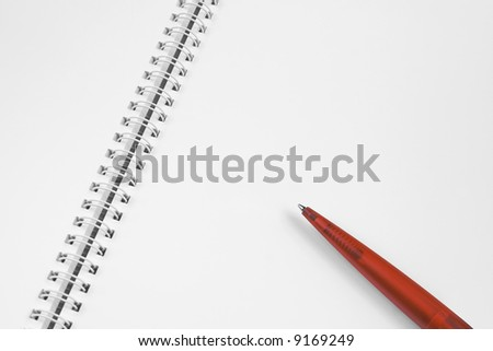 Open, blank spiral notebook with red plastic pen. - stock photo