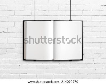 Open blank textbook on white brick wall - stock photo