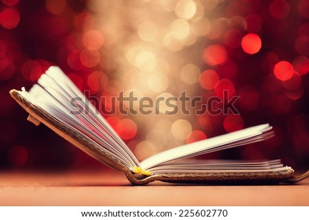 Open book against color defocused lights background - stock photo