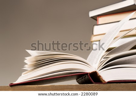 open book and a few books in stock on second plan