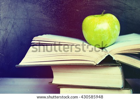 Open book and a green apple in front of blackboard