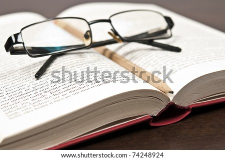 Open book and eyeglasses on desk - stock photo