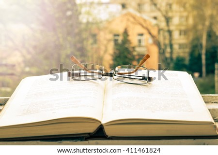 Open book and glasses. Nice view from the window. Trees and sun. - stock photo
