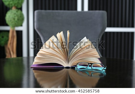 Open book and glasses on wood table. Education background. - stock photo