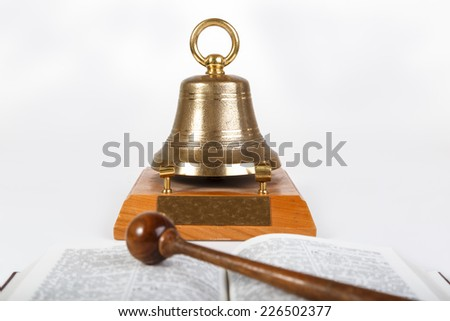 Open book and meeting bell on table