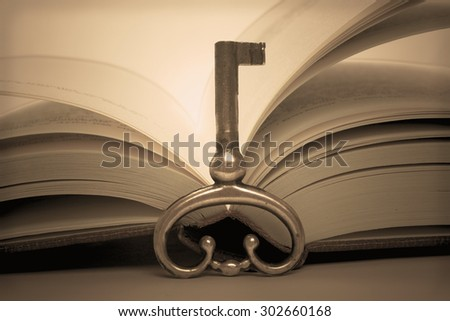 Open book and old metal key - retro image - stock photo